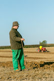Old farmer with stick and tractor at ploughing match stock image