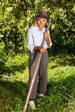 Old farmer using scythe to mow the grass Royalty Free Stock Photography