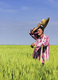 Old farmer wipe the sweat on break from work in field Royalty Free Stock Image