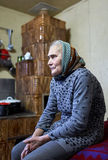 Old farmer woman indoor. Senior peasant farmer woman sitting in her home Stock Photography