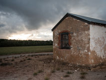 Old farmhouse building at dusk. Eerie old building at dusk under a stormy sky Royalty Free Stock Image