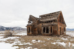 Old farmhouse, Sierra Valley, California. Old wooden farmhouse in decay in snow covered countryside of Sierra Valley, California, USA Stock Image