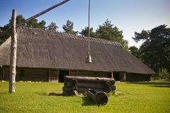 Old farmhouse and a well. Traditional thatched roof farmhouse and a well, located in Estonia, National Open Air Museum stock image