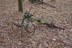 Old farming tools on the ground. Old farming tools sitting on the ground with foliage on it stock image