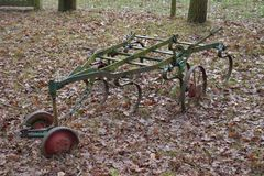 Old farming tools on the ground. Old farming tools sitting on the ground with foliage on it royalty free stock images