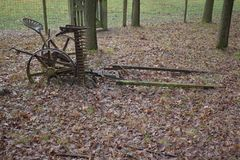 Old farming tools on the ground. Old farming tools sitting on the ground with foliage on it royalty free stock photo