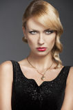 Old fashion blond girl, in front of the camera. Young elegant blond woman wearing black dress with an old fashion hairtyle and necklace jewellery, she is in Stock Images