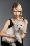 Old fashion blond girl,she has a dog in her arms. Young elegant blond woman wearing black dress with an old fashion hairtyle and necklace jewellery, she looks Stock Images