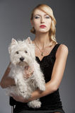 Old fashion blond girl,she has a dog in her arms. Young elegant blond woman wearing black dress with an old fashion hairtyle and necklace jewellery, she is in Royalty Free Stock Photos