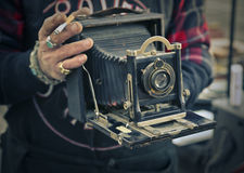 Old fashion camera. Man holding an old fashion camera royalty free stock photography