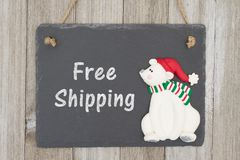 Old fashion Christmas free shipping message. A retro chalkboard with a polar bear hanging on weathered wood background with text Free Shipping stock photos