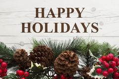 Old fashion Christmas greeting. Garland with pine cones and red holly berries on weathered wood background with text Happy Holidays Stock Photography