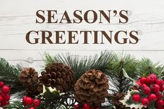 Old fashion Christmas greeting. Garland with pine cones and red holly berries on weathered wood background with text Season`s Greetings Stock Photos