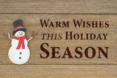 Old fashion Christmas message for Holiday Season. Old fashion Christmas message, A retro snowman on weathered wood background with text Warm Wishes this holiday Royalty Free Stock Images