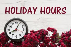 Old fashion Christmas store message. Frost covered red holly berries with an alarm clock on weathered wood background with text Holiday Hours Royalty Free Stock Image