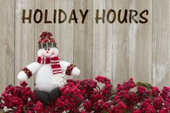 Old fashion Christmas store message. Frost covered red holly berries with a snowman on weathered wood background with text Holiday Hours Royalty Free Stock Photo