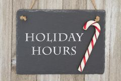 Old fashion Christmas store message. A retro chalkboard with a candy cane hanging on weathered wood background with text Holiday Hours Royalty Free Stock Image
