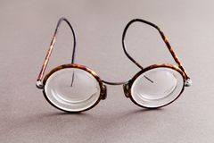 Old fashion design spectacles eyeglasses on gray paper background. Vintage style men fashion accessories. Macro view. Shallow depth of field, soft focus Stock Photo