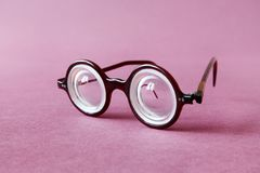 Old fashion design spectacles eyeglasses on pink violet paper background. Vintage style men fashion accessories for Stock Images