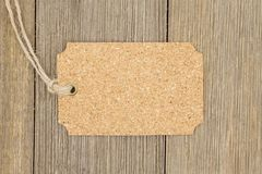 Old fashion gift tag. A retro cork gift tag on weathered wood background with copy space for your text Royalty Free Stock Photos