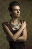 Old fashion girl with necklace. Vintage portrait of beautiful young woman in elegant old fashion purple dress , important necklace looking on one side Stock Photos