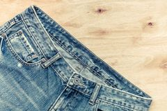 Old fashion jeans. On wood background Royalty Free Stock Photo