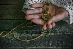 Old fashion lady holds a golden key in her hands. Space for text royalty free stock image