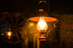 Old-fashion lamp lighting on the dark background. With a wheel and brick wall Royalty Free Stock Photography
