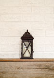 Old fashion latern on a wooden mantel. A lantern resting on a wooden mantel set against white brick Royalty Free Stock Image