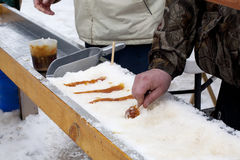 Old Fashion Maple Taffy on Snow. A very old way of using heated maple syrup to make a treat from Stock Photos