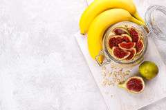 Old fashion oats. With greek yogurt , banana and figs in a jar on white rustic background Stock Photos
