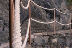 Old fashion with a rope handrail in the cinque terre. It is used to help people to explore the famous coasts and cliff stock photography