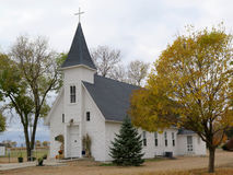 Old Fashion White Church with a Steeple. An old rustic white church sits in the countryside with a steeple and cross on top stock photography