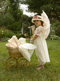 Old Fashion Young Lady. Small girl enjoys the old fashion attire while pushing baby-doll buggy Stock Image