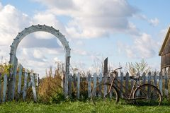 Old Fashioned. A rusted old bike leans against a ramshackle old fence, while a dilapidated gateway leads to a beautiful blue sky with puffy white clouds Royalty Free Stock Image