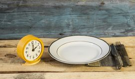 Old fashioned alarm clock and white plate with fork and knife Royalty Free Stock Photography