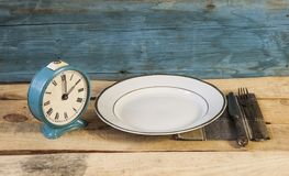 Old fashioned alarm clock and white plate with fork and knife Stock Photos