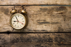 Old fashioned alarm clock on wooden background Stock Photos