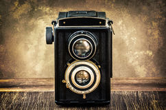 Old fashioned antique camera in vintage style. With filtered textured background stock image