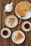 Old-fashioned apple pie with black tea. On wooden background Stock Images