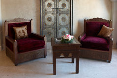 Old-fashioned armchair and table with flowers Royalty Free Stock Image