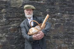 Old fashioned 1940 baker with bread basket. Outdoors royalty free stock image