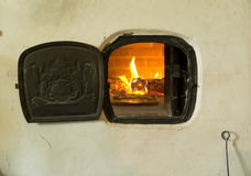 Old fashioned baking. Baking biscuits the old fashioned way in a fire stove enclosed in a wall Stock Photography