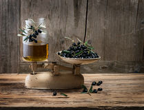 Old-fashioned balance scale with olives and olive oil Stock Photos