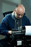 Old fashioned bald writer in glasses. Writing book on a vintage typewriter Royalty Free Stock Photo