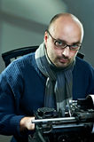 Old fashioned bald writer in glasses. Writing book on a vintage typewriter Stock Photos