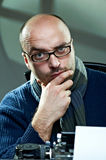 Old fashioned bald writer in glasses. Writing book on a vintage typewriter Royalty Free Stock Photos
