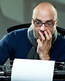 Old fashioned bald writer in glasses. Writing book on a vintage typewriter Stock Image