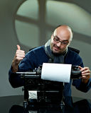 Old fashioned bald writer in glasses. Writing book on a vintage typewriter Royalty Free Stock Images