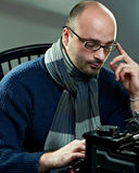 Old fashioned bald writer in glasses. Writing book on a vintage typewriter Stock Images